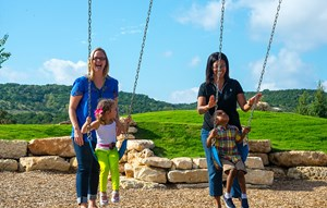 Sweetwater Austin Club Playground  - Parents and Kids on Swings